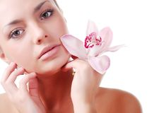 Face of woman and orchid. Face of beautiful young woman with delicate orchid Stock Photo
