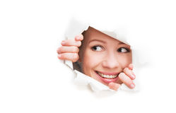 Face of  woman peeking through a  hole torn in white paper poste. Face of a young curious woman peeking through a  hole torn in white paper poster Royalty Free Stock Photos