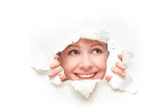 Face of woman peeking through a hole torn in white paper poster. Face of a young curious woman peeking through a hole torn in white paper poster stock image
