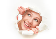 Face of  woman peeking through a  hole torn in white paper poster Stock Photo