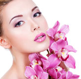 Face of a woman with purple eye makeup and lips. Closeup face of an young beautiful woman with a purple eye makeup and lips. Pretty adult girl with flower near stock photos