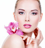 Face of a woman with purple eye makeup and lips. Closeup face of an young beautiful woman with a purple eye makeup and lips. Pretty adult girl with flower near stock photography