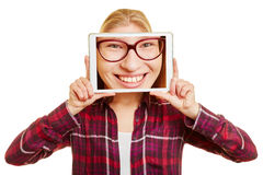 Face of a woman on a tablet. In front of a woman`s head Stock Photography