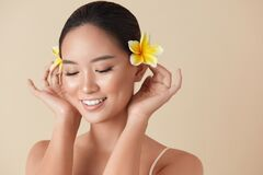 Free Face. Woman With Flowers Portrait. Beautiful Asian Model With Plumeria In Hair Posing Against Beige Background. Royalty Free Stock Photo - 187879015