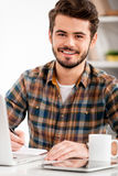 Face of work satisfaction. Smiling young man writing in note pad and looking at camera while sitting at his working place Royalty Free Stock Photography