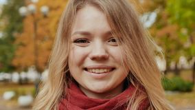 Face of young attractive girl close-up. Smiling girl posing on camera among colorful autumn park trees. Face of young attractive girl close-up. Smiling girl stock footage