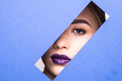 Face of young beautiful girl with a bright make-up looks through a hole in violet paper. Close up beauty portrait. Face of young beautiful girl with a bright stock photo