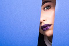 Face of young beautiful girl with a bright make-up looks through a hole in violet paper. Close up beauty portrait. Face of young beautiful girl with a bright royalty free stock images
