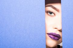TTe face of a young beautiful girl with a bright make-up and with plump violet lips peeks into a hole in purple paper. Cosmetics,. The face of a young beautiful stock image