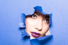 The face of a young beautiful girl with a bright make-up and puffy purple lips peers into a hole in purple paper. The face of young beautiful girl with a bright royalty free stock images