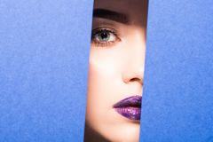 Face of young beautiful woman with a bright make-up and violet lips looks through a hole in violet paper. Face of young beautiful girl with a bright make-up and stock photos