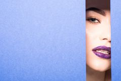 Face of young beautiful woman with a bright make-up and violet lips looks through a hole in violet paper. Face of young beautiful girl with a bright make-up and royalty free stock photography