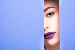 Face of young beautiful girl with a bright make-up and violet lips looks through a hole in violet paper. Closeup beauty portrait. Face of young beautiful girl stock image