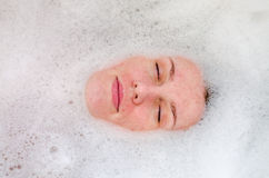 Face of a young beautiful girl in a white bath among soap bubbles from the foam bath gel, naked with wet hair, enjoys the spa trea Royalty Free Stock Images