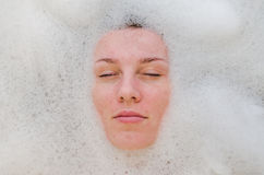Face of a young beautiful girl in a white bath among soap bubbles from the foam bath gel, naked with wet hair, enjoys the spa trea Stock Photography