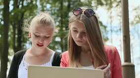 Face of young beautiful girls College girls with laptop in hand in the green park. Closeup. Face of young beautiful girls College girls with laptop in hand in stock video footage