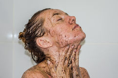 Face of young beautiful sexy girl with long hair girl who takes a bath naked in the spa procedures, wellness dealt a protective ma Stock Images