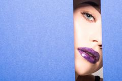 Face of young beautiful woman with a bright make-up and violet lips looks through a hole in violet paper. Face of young beautiful girl with a bright make-up and royalty free stock image