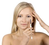 Face of young blonde woman + scalpel in her hand stock image