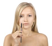 Face of young blonde woman + scalpel in her hand stock images