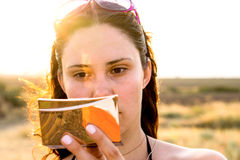 Face of young brunette girl with cosmetic mirror in bright sun rays. Warm filtered Royalty Free Stock Photo
