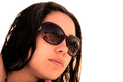 Face of young brunette girl in sunglasses with beach reflection in bright sun rays. Warm filtered Stock Images