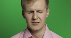 Face of young depressed man crying on green chroma key background stock photo