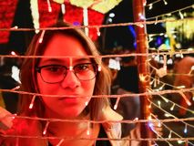Face of a young girl at a Christmas fair with colorful lights stock image
