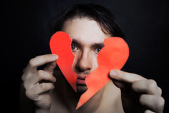 Face of young handsome man with broken paper heart Stock Photo