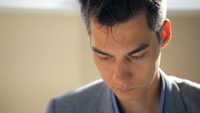 Face of young man, which shine from behind sun, sits in a gray jacket, his head bowed down, close-up. stock video footage