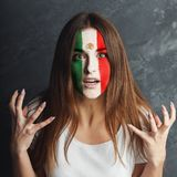 Young woman with Mexica flag painted on her face. Face of young sad woman painted with flag of Mexica. Football or soccer team fan, sport event, faceart and Royalty Free Stock Image