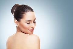 Face of young woman with clean skin on a blue gray bac Royalty Free Stock Image