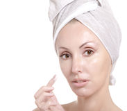 Face of the young woman close up. The beautiful young woman in towel with a cosmetic cream Royalty Free Stock Photo