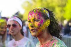 Face of young woman with colored powder Royalty Free Stock Photo