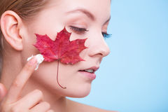 Face of young woman girl with red maple leaf cream Stock Photos