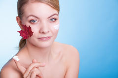Face of young woman girl with red maple leaf cream Royalty Free Stock Images