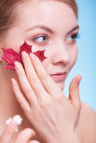 Face of young woman girl with red maple leaf cream Stock Image