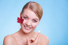 Face of young woman girl with red maple leaf cream Royalty Free Stock Photo