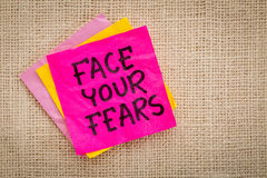 Face your fears advice on sticky note Royalty Free Stock Photo