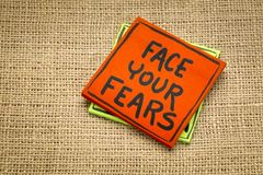 Face your fears reminder note. Face your fears reminde - handwriting on a sticky note against burlap canvas royalty free stock photo
