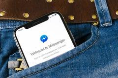 Facebook信使在苹果计算机iPhone x屏幕特写镜头的应用象在牛仔裤装在口袋里 Facebook信使app象 网上实习生 库存图片