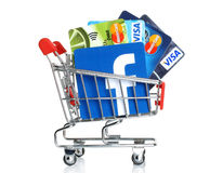 Facebook商标打印在纸和被安置入有卡片签证的购物车和万事达卡在白色背景 图库摄影