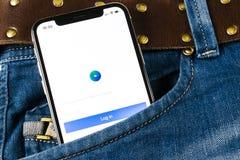 Facebook广告在苹果计算机iPhone x屏幕特写镜头的应用象在牛仔裤装在口袋里 Facebook企业app象 流动Facebook的广告 库存照片