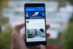 Facebook探索在手机的饲料 免版税库存照片