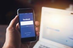 Facebook App στο iPhone με το υπόβαθρο lap-top υπολογιστών Στοκ φωτογραφίες με δικαίωμα ελεύθερης χρήσης