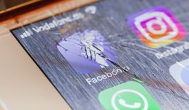 Facebook app on broken iPhone screen. BERLIN, GERMANY - OCTOBER 15, 2018: Facebook app on a broken screen of an iPhone 7 Plus with personalized background stock images