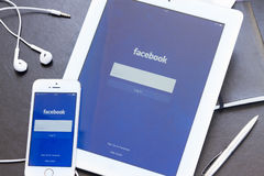 Facebook app na tela de Ipad e de Iphone 5s. Fotos de Stock Royalty Free
