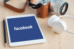 Facebook app op de vertoning van Apple ipad en de mirrorless camera stock fotografie