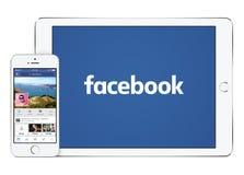 Facebook app på vit Apple iPadluft 2 och iPhonen 5s Fotografering för Bildbyråer