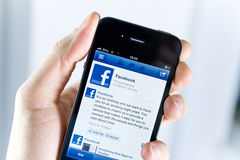 Facebook Application On Apple iPhone. A man holding Apple iPhone4 with a Facebook application on the screen Royalty Free Stock Photography